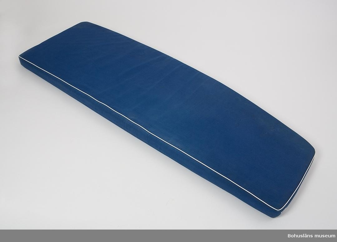 Madrass för styrbords koj  i salongen/kajutan/ruffen. Formskuren skumgummidyna klädd med mörkblå kanvas. Övre kanten skodd med vit plastpasspoal. Fläckar av saltvatten, något blekt.  Vindö 22 nr 10 ANNOVA levererades sommaren 1968.  ANNOVA är en fin representant för övergången från trä till plast inom båtbyggeriet. Skrovet är tillverkat i glasfiber, men däcket är av teak, och överbyggnad och inredning av mahogny.  Trävirket och hantverket är av högsta kvalitet. Skrovlängden är 7,10 m och bredden 2,15.  Masten är av aluminium. ANNOVA är fortfarande i originalskick.  Hon har hela tiden haft en och samma ägare,  professor Carl-Gustav Engström med familj.  Vindövarvet, ett av Orustområdets legendariska båtvarv, startades 1926 av Carl Andersson.  Han var både en skicklig hantverkare och konstruktör.  Varvet byggde olika bruksbåtar, men med tiden satsades allt mer på kappseglingsbåtar. Under 1950-talet var Folkbåtar den stora produkten. Just Folkbåten hade blivit en omtyckt familjebåt.  Men många ville ha en något större båt som passade bättre för havssegling. Det ledde till att Carl 1961 konstruerade en båt kallad Vindö 28. Den blev en milstolpe i varvets historia och var den första i raden av olika Vindöbåtar som gjorde varvet välkänt i både Sverige och utomlands.  Erfarenheter av plast fick Vindövarvet från 1960, och det nya etablerades på allvar när man 1965 började producera Vegan. Den var konstruerad av Per Brohäll, och blev oerhört populär. Plastskroven gjordes inte på Vindövarvet, utan köptes in från Lysekils Båtvarv, senare från Lyse Plastprodukter. När Vindö 22:an levererades hade Carls son Karl-Erik Andersson övertagit uppgiften som varvets ledare, men Carl satt kvar vid ritbordet.