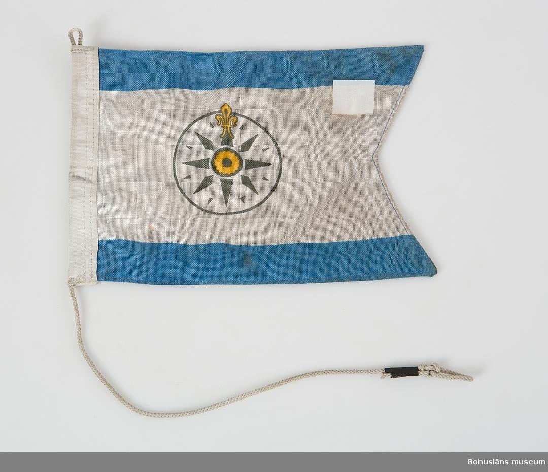 Tvåtungad mindre viimpel med flagglina. Svenska Kryssarklubbens emblem med kompassros. Blå längsgående linjer i över- och underkant.