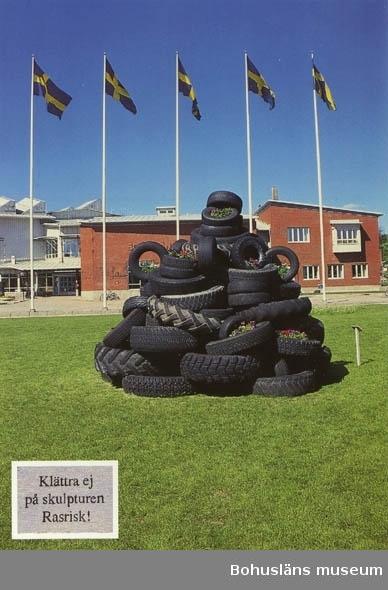"""Vykort. """"Uddevalla: Den nya däckskulpturen på gräsmattan framför museet"""""""
