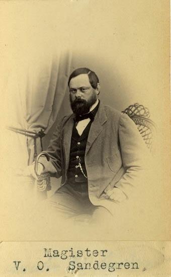 """Text på kortets baksida: """"Magister Viktor Ossian Sandegren, f. 1823 i Weddige, pastorsson. Magister i Lund 1853. Collega i Strömstad 1857. Do Uddevalla 1859. Läroverksadjunkt i Göteborg 1868. Död 1879 25/4. Gift m. A. S. Lind""""."""