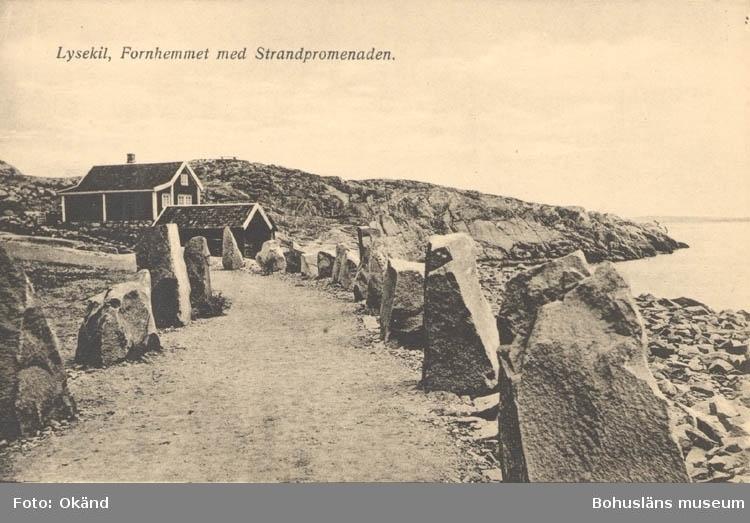 """Tryckt text på kortet: """"Lysekil. Fornhemmet med Strandpromenaden."""" """"Lysekils Pappers- & Musikhandel. (Gerda Ohlsson)."""""""