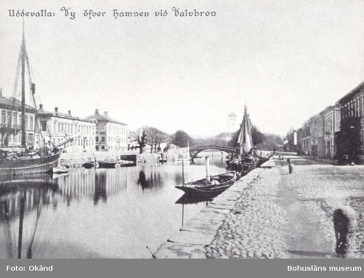"""Tryckt text på kortet: """"Uddevalla. Vy öfver hamnen vid Valvbron."""" """"Reproduktion av foto tillhörande Uddevalla Museum."""""""