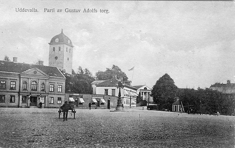 """Tryckt text på vykortets framsida: """"Uddevalla Parti av Gustav Adolfs torg""""."""