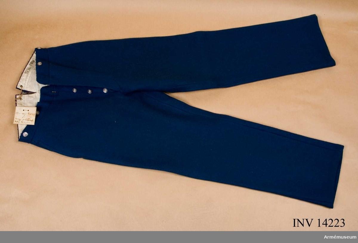 """Grupp C I. Byxor av ljusblått kläde - långa med två fickor på sidan och på baksidan spänningstamp av kläde med spännen. Järnknapparna är: fyra st på sprundet och dito för hängslen. Foder av vitt tyg med stämpel: """"PRM - prövemaessigt - modellenligt 1913"""". (Munderingsvaesenet i Fredstid. Första Hefte. Kjöbenhavn 1908. sid 30 paragraf 54 Stempler). Byxorna har pappersetikett med påskrift: """"Anmiddige benklaeder for menage af Fodfolket"""". Ankom 1914-02-20. På andra sidan stämpel med krona och """"Materiel Intendenturen"""". Litteratur: Enl. Handbuch der Uniformkunde, Rickard Knötel Hamburg 1937, sid 142. År 1850 infördes i danska armén dubbelknäppt vapenrock och långa byxor av ljusblått kläde. Armeenalbum I. Die Daenische armee. Leipzig. Verlag von Moritz Ruhl. Sid 8. Infanterie - uniformsbeskrivning. Byxor är av ljusblått kläde. Bilaga sid 3. Infanteriet i likadana byxor. Danska Uniformer, Haer og flaade, tegnede af Rs. Christiansen, Kjöbenhavn, troligen 1912. Album i färger. Infanteriet i ljusblå byxor.Granberg."""