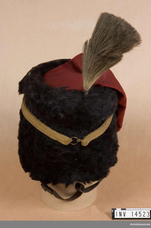 """Grupp C I. I bruk ännu år 1913.Tolpak (turk. kalpak) av svart päls, 19 cm hög. Övre delen är betäckt med mörkt rött kläde och har en pung (Beutel), 20 cm lång, på vänstra sidan. Foder av gult bomullstyg. Svettrem av svart läder och svart tyg, botten är av läder på vilken en papperslapp finns fastklistrad med påskriften (firmanamn och adress) """"Almon Accantrement Maker, and Saddler 14, St Jamesele street, London. Size 22 3/1"""". På tolpakens baksida vid övre kanten finns ståndhållare av mässing med skruv för plym. Tolpak har hakremmar som är fastsydda på båda sidor och har järnspännen. Runt omkring tolpaken finns ett bälte av gula snören, som stänges med hake och ringen på andra änden. Med vit tagelståndare. Litteratur: Handbuch der Uniformkunde. prof. R. Knötel. Hamburg 1937, sid 214. Artilleri. Efter år 1837 ridande artilleriet hade fått tolpak (Tels Mutze) med röd pung (Beutel), vit plym och gula fångsnören. Sid 213: Ridande artilleriet hade från år 1815 till första världskrigets början (1914) likadan uniform utan någon förändring. Die Heere und Flotten der Gegenwart, Grossbritannien und Irland, G. von Zepelin, 1897, Leipzig, sid 49: Uniformen för ridande artilleri bestod av kort mörkblå dolma, mörkblåa byxor och pälshatt med röd pung (Beutel) och vit plym."""