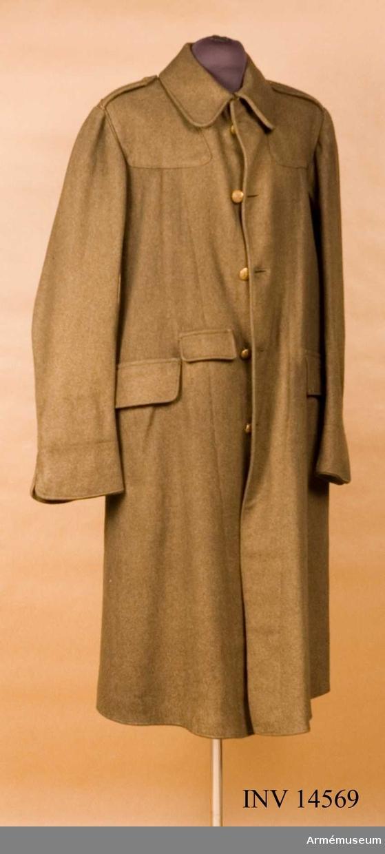 """Grupp C I. Benämning överrock för menig. England. Överrock av khakifärgat kläde, enradig (5 knappar). Baktill i livet en sleif som består av två delar, en med 3 knäpphål och dess andra med 3 knappar: en slits - 50 cm lång med 2 knapphål och knappar. Vid axelklaffarna och bröstets övre del finns fastsydda förstärkningar av samma kläde.  Axelklaffar av samma kläde, 7 cm breda och 13 cm långa och fastsydda vid ärmsömmarna, samt fästes vid överrocken med knappar av mindre format.  Fickor -två- sido- raka, 23 cm långa med lock som stänges med små benknappar på inre sidan. En liten ficka på framsidan, 10 cm bred med lock. Foder saknas. På klädets inre sida finns en stämpel: """"8.9 - 10"""", """"7"""" (troligen storlek) och en påklistrad papperslapp med skrift (firmans ettikett): """"Cloth Mixture """"Service dress"""" Dismounted"""" - blandade kläder """"tjänste dress"""" dismonterad. """"Size Nr: 7 - storlek Nr 7. """"Height 5 ft 9 & 10"""" - höjd. """"Brest 38 to 40 - bröst. På vänstra sidan rund stämpel (fabriksstämpel) men påskriften oläslig. Knappar alla av metall, guldfärgade, 25 cm i diameter. 5 st på framsidan. På knapparnas baksida står: """"Birmingham. Firmin & Sonsl."""". På axelklaffarna sleif och slits - 7 cm, 1,7 cm i diameter, på baksidan står: """"W Twigg & Co"""", """"Birmingham."""" På alla knappar engelska statsvapnet. Krage - liggande, med hyska och hake. Underkragen är möjlig att knäppa med hjälp av benknappar och en sleif. Ärmuppslag - 10 cm höga med avrundande vinklar."""