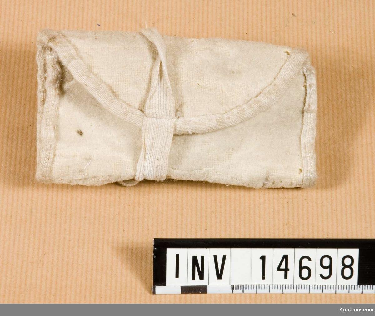 Grupp nr C II. Samhörande nr är 14697-14707. Syväska. England. Sysäck av vitt kläde med två fickor för tråd, nålar, knappar och fingerborg (som är av järn). Säcken stänges med två bomullsband.