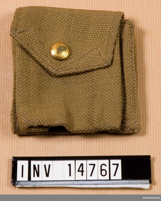 """Patronväska, för 5 patroner. England. 1913. Grupp C II. Patronväska av khakifärgat tjockt bomullstyg (på engelska  wibbing) försedd med lock, som stänges med en knapp av mässing. På undersidan av patronväskans lock finns en stämpel: """"M.E.Co. 1913"""". På patronväskans baksida finns två smala hylsor, med vilka väskan fästes vid livremmen. Enligt kapten W. Granberg."""