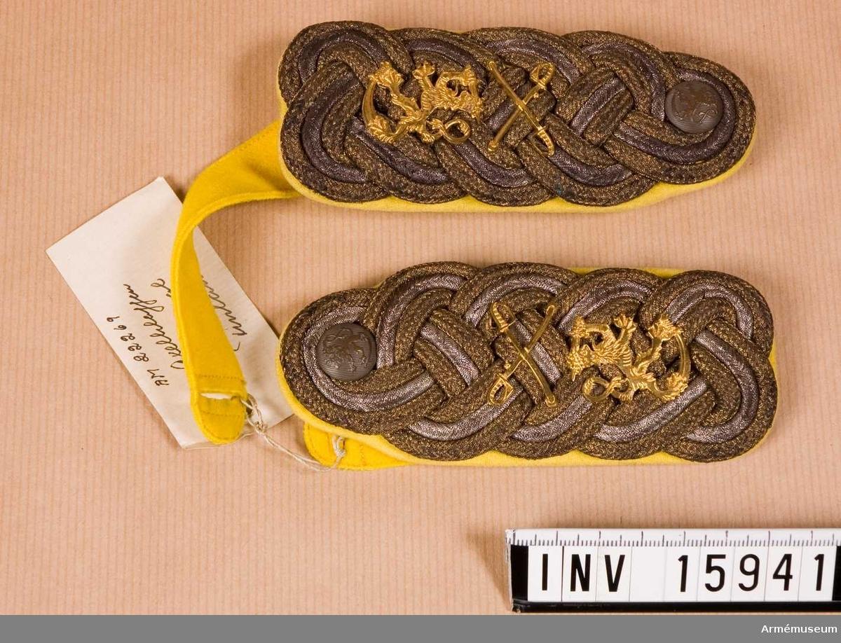 """Grupp C I. Axelklaffar av flätade tränsar i oxiderat silver och guld; på  botten kläde i gul färg (generals i kavalleriet axelklaffar). Längd 12 cm och bredd 4,5 cm. På nedre delen av axelstycket rikslejonet i guld, upptill två korslagda sablar (kavalleriets emblem på axelstyckerna) av gul metall. På övre delen av axelklaffarna, knappar av vit metall, gråfärgade mindre storlek, vapenprydda. På baksidan - platta krokar av gul metall för att knäppa axelklaffarna till vapenrocken. På platta krokarna står: """"Holts gulddrageri, Stockholm"""". Axelklaffarna  ha remsor av gult kläde. Litteratur: Enligt Republikens presidents beslut om  uniformsbeklädnad för rikets krigsmakt, Försvarsministeriets Förlag. Helsingfors 1922. Sidan 5, 24 - axelstyckens bottenfärg för kavalleri - gul. I bilaga sidan 18, ritning 71. Sidan 28, ritning 173 emblem för kavalleri - korsade sablar."""