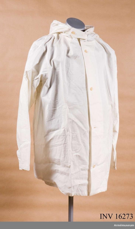 Av vitt bomullstyg med knäppning fram och med kapuschong.