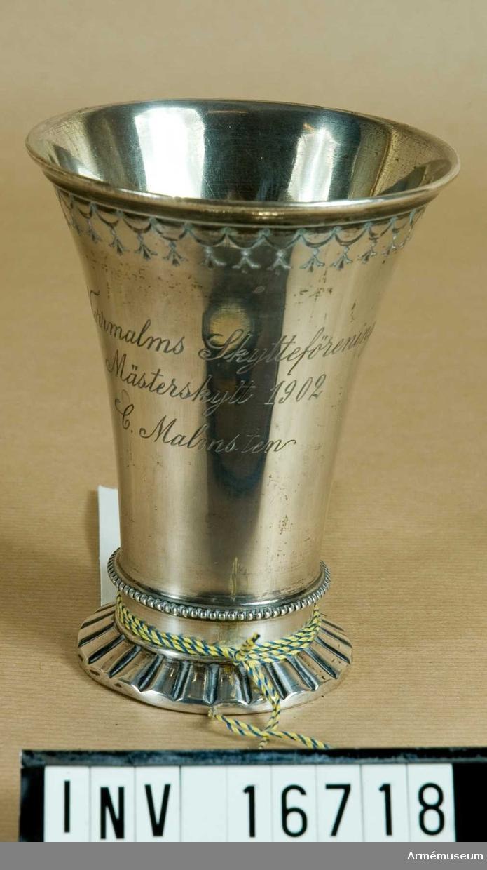 Norrmalms Skytteförenings Mästerskytt 1902 C. Malmsten. En silverbägare som är utsvängd upptill med en ornerad kant. Foten skall göra intryck av att vara veckad och har vid övergången mot foten en pärlrand.