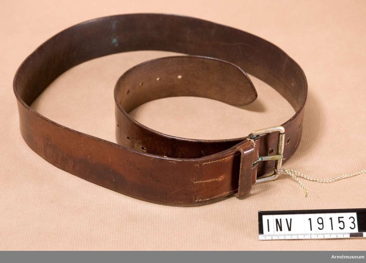 Samhörande nr är 19145-60, rockar, byxor, mössa, livremmar, m m personlig utrustning. Av brunt läder med metallspänne med ett torn.