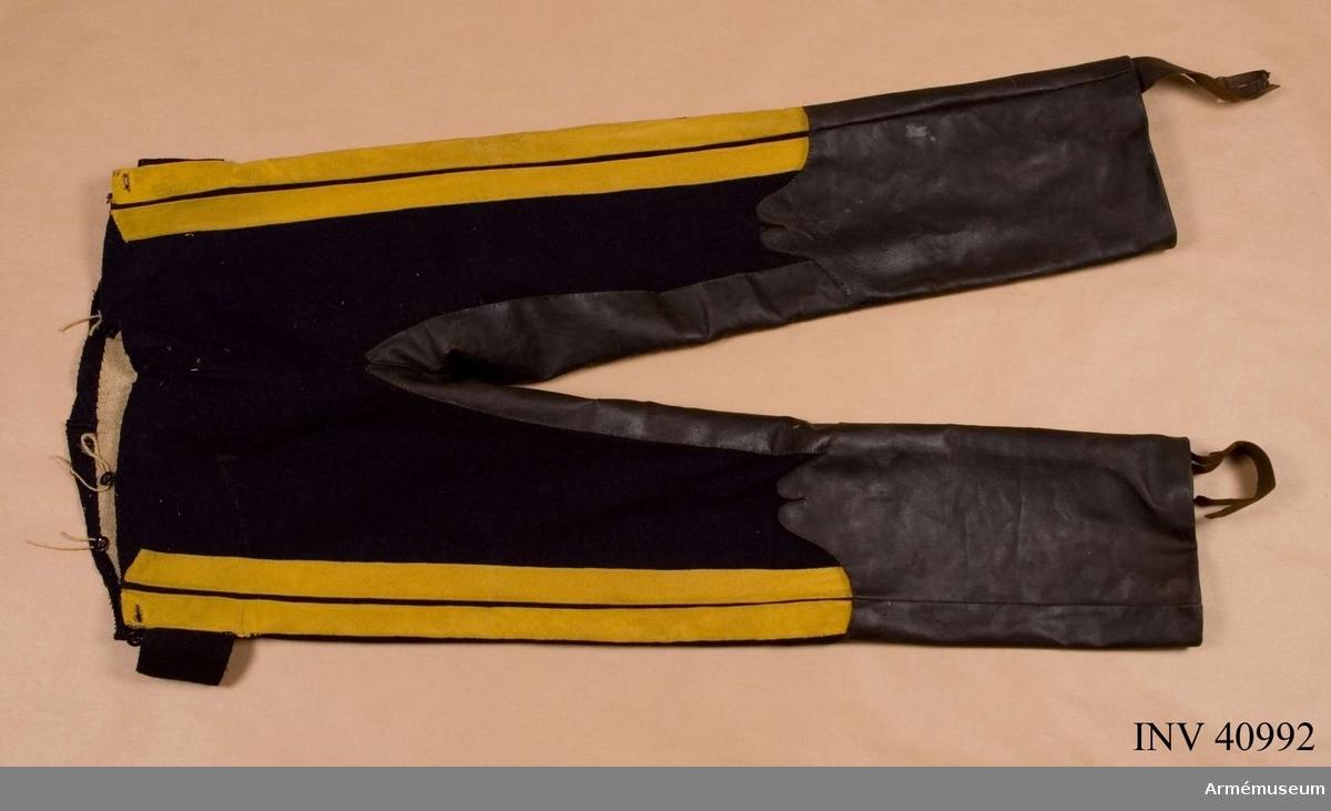 Grupp C Består av kollett, byxor, stallmössa, stövlar med sporrar. Livplagg m/1835. Tillverkade av två valltrapper för manskapshäst enligt KAID skr. 2/7 1896. Av mörkblått kläde med två gula lister i sidorna. Grenskinn och stövelskoning. Fodrade med grått linne. Hällor av läder.  Samhörande nr: AM.40991-5
