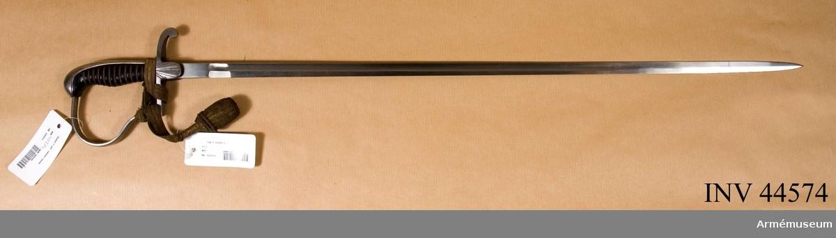 Samhörande nummer är 44574-6, sabel, balja, portepè. Grupp D II. Klingans bredd upptill är 19 mm.Klingan är rak. Upptill har den en 55 mm lång, fyrkantig ansats. I övrigt är den till större delen eneggad och skålslipad, men 210 mm ovanför udden får den ryggar och blir tveeggad. Fästet är av järn. Kaveln är klädd med svart skinn. Litet ovanför mitten är den starkt utsvängd på framsidan och upptill bildar den en sorts framåtböjd knapp. Kring kaveln går en spiralreffla 13 varv. Baktill har kaveln ryggbeslag, som upptill  övergår i en framåtböjd, avrundad kappa. Längst ned går kring  kaveln och ryggbeslaget ett kullrigt, 95 mm brett järnbeslag. Parerstången är rak och har rektangulärt tvärsnitt. På mitten är den något bredare än kaveln, men sedan avsmalnar den litet mot framänden och ganska mycket mot bakänden. Längst bak är  parerstången nedåtböjd och avslutas med en nedåtriktad knapp.Från parerstångens mitt utgår på vardera undersidan en 22 mm bred och 26 mm lång, nedtill avrundad styrskena, som har bräckta kanter. Yttersidans styrskena är prydd med solfjädersformigt utgående refflor. Från parerstångens framände utgår handbygeln i nära nog rät vinkel. Den går uppåt omkring 30 mm, men där svänger den i en kraftig bukt framåt och går sedan bakåt. Handbygelns övre ände är instucken under kappans framkant. Handbygeln har närmast rektangulärt tvärsnitt, dock med kulllrig fram- och baksida, samt är i det närmaste jämnbred.Sabeln skänktes till Göta gardes museum år 1934 av friherrinnan Ebba Rudbeck. Den uppgives ha förts under 1864 års krig av d.v. löjtnanten vid Andra Livgardet Friherre Z. Rudbeck.