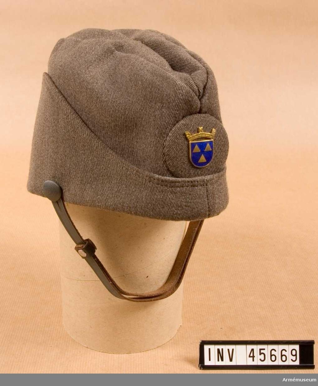 Barett i mörkblå sammet.Grupp C I.Ur tjänstedräkt m/1942 för kvinnliga bilkåren. Består av jacka,  kjol, fältbyxor, fältmössa, barett, två blusar, två slipsar, manschettknappar, handskar.Uniformen är av den typ som användes i landsorten. Stockholms bilkårister hade en mera blågrå uniform med längre jacka och påsydda fickor. Baretten användes vid riksmöten, årsmöten och större fester.  Fältmössan användes i tjänst.  Samhörande nummer är AM.045665-AM.045675, tjänstedräktspersedlar.