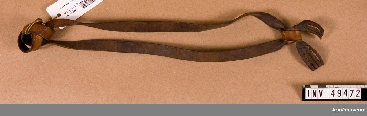 Grupp D I.   Av brunt läder, slagen två gånger kring skaftet. Armslingans  fria ände är hopknuten och de bägge remändarna är på andra sidan  om knuten kluvna i tandade fransar.