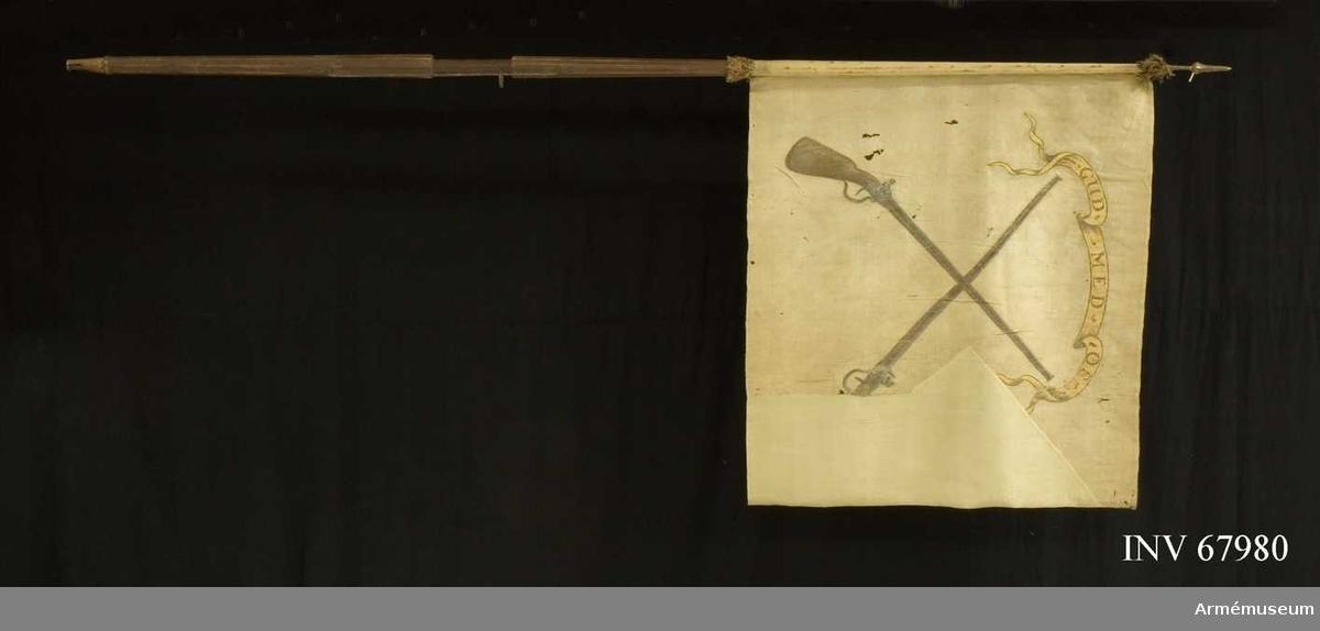 """Duk: Tillverkad av enkel vit sidentaft, sydd av en våd. Tvåtungad. Frans i svart, rött och vitt silkeenbart vid duken. Kanter vid stången. Duken fastsydd runt stången.  Dekor: Målad lika på båda sidor, två korslagda flintlåskarbiner. Över dessa ett gyllene inskriptionsband med bruna bokstäver. Bandet med bruna konturer.   Stång av brunmålad furu. Kanellerad ovanför greppet, fasetterad nedanför. Saknar doppsko. 100 mm nedifrån ett läderband fäst med nitar.   Spets eventuellt av silver. Löpande bärring. Löparen fäst långt ovanför och nedanför greppet med två spikar på vardera stället. Spets av mässing i ett stycke fäst med två spikar (T.Lenk).  Märkning:  Etikett på stången strax under duken (borttagen och lagd i kuvert): """"No 115"""", """"l standar"""", """"k: ad Frederics)""""."""
