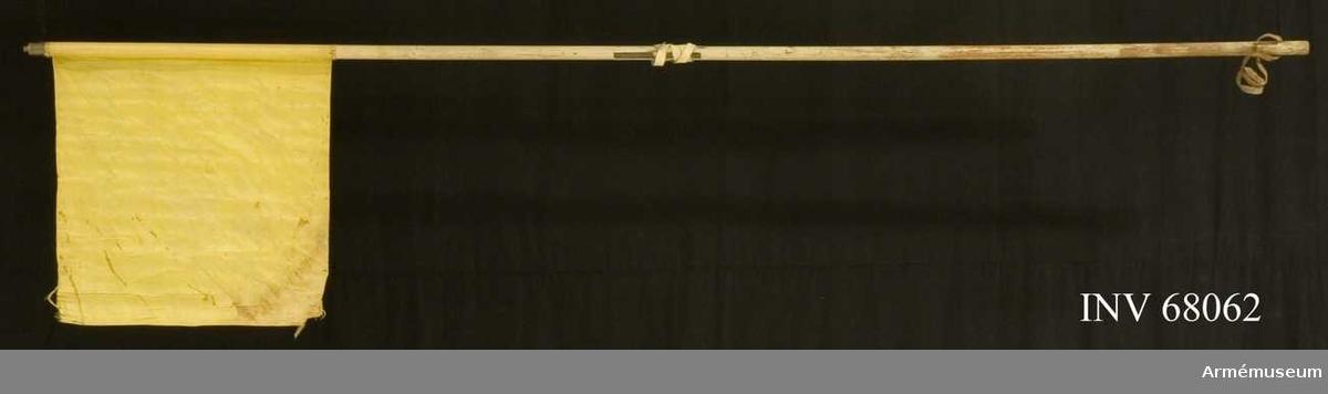 Duk: Enkel, tillverkad av enkel, citrongul sidentaft. Fållen lagd åt dukens utsida. Duken fäst med en rad tennlickor på gult, mönstervävt band.  Dekor: Saknas   Stång av trä, vitmålad. Holk finns, men ej spets.   En ljus skinnremsa instucken 680-700 mm mätt från dukens fäste. I nedre änden en mörk rem instucken 50-70 mm mätt från nedre änden, bildande en ögla, 250 mm lång.