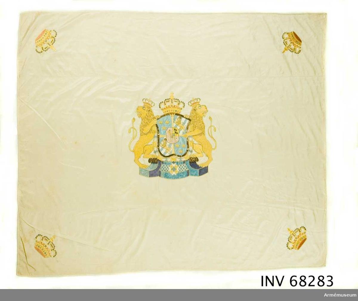 Duk: Tillverkad av enkel vit sidenkypert, sydd av tre horisontella våder. Duken kantad med ett mönstervävt sidenband.  Dekor: Broderad, lika på båda sidor, Stora riksvapnet. I hörnen broderade slutna kronor 130 x 165 mm.