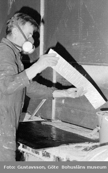 "Motivbeskrivning: ""Gullmarsvarvet AB, på bilden syns Lars Samuelsson som rullar plast på glasfiberremsor."" Datum: 19801031"