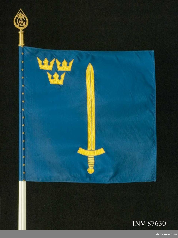 Kommandotecken bestående av standarstång med doppsko, duk, holk och spets. Duk av blått fansiden. Motiv av svärd och kronor som applikation och maskinbroderat. Duken fäst vid stången med en rad gropiga tännlikor. 18 + 2 st. Delbar stång. Spets med Gustav VI Adolfs monogram.