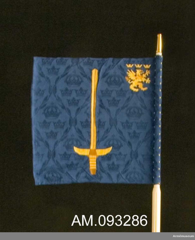 På blå duk ett stolpvis ställt gult svärd, i övre inre hörnet en upprest grip under tre bjälkvis ordnade öppna kronor, allt i gult. Duk av blått damastvävt fansiden. Handbroderad i intarsia.