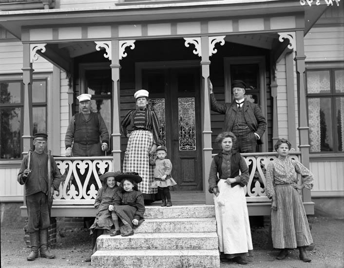 """Enligt tidigare noteringar: """"Verand på manbyggnaden. Gruppfoto på folk vid verandan. Snickeridetaljer."""""""