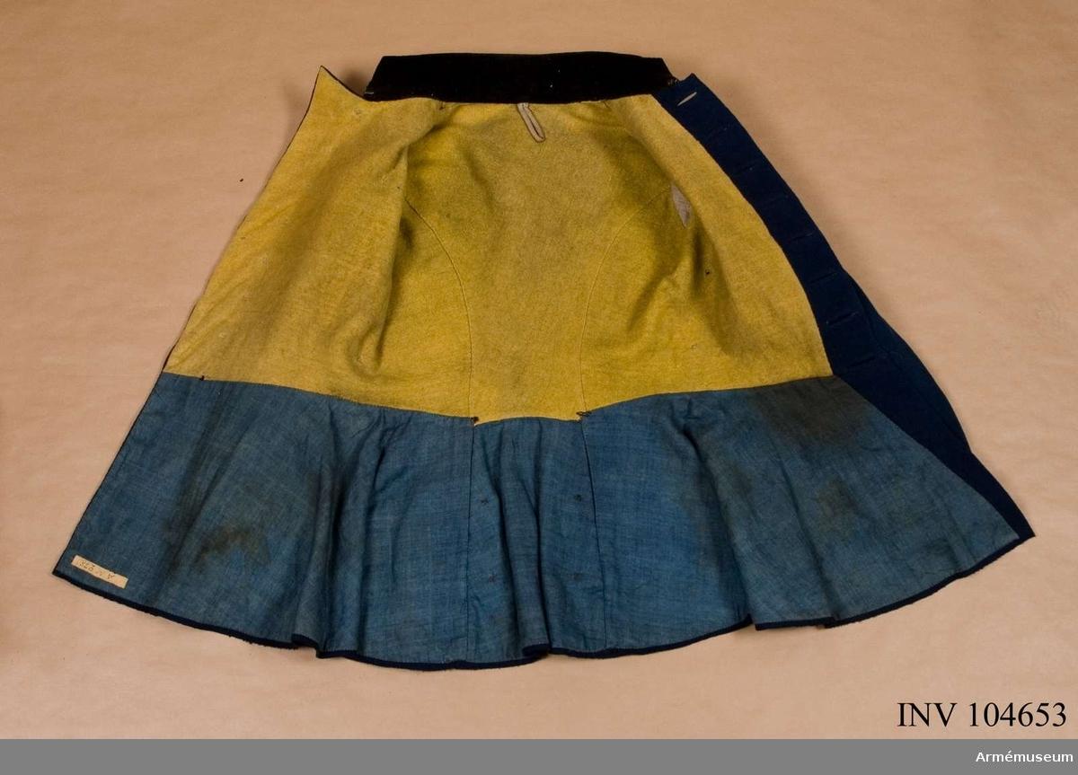 Grupp C I.  Vapenrock, go 30/12 1854.  Vapenrock av mellanblått kläde, enkelknäppt med 8 kullriga mässings knappar. Kragen, som är snedskuren, är av svart kläde och försedd med s. k. knapphål av gula redgarnssnören. Axelklaffar av svart kläde med gul paspoal samt fodrade med mellanblått kläde. Skörtet är baktill försett med 6 mässingsknappar. I sidorna sitter slejfer, varigenom livremmen träds. Ärmuppslagen är av svart kläde och försedda med 3 blindknapphål och knappar, varav 2 knäppta. Halva rocken är fodrad med gult, tuskaftat ylle, skörtet med blått, tuskaftat linne och ärmarna med grått d:o.