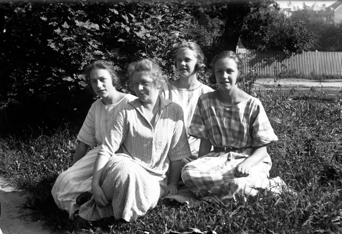Fyra kvinnor sitter i gräset vid ett träd, i bakgrunden syns hus och ett staket.