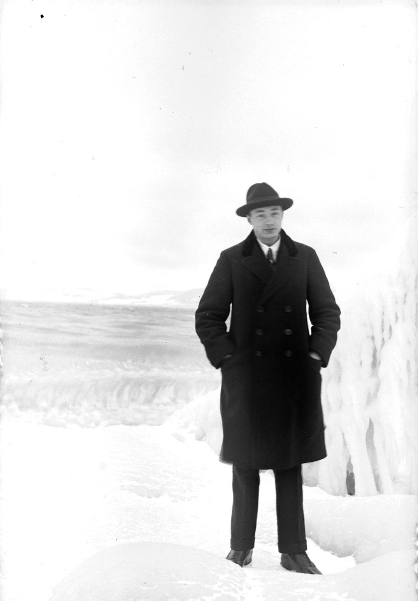 Gustav Andersson står vid en sjö med en isformation bredvid sig.