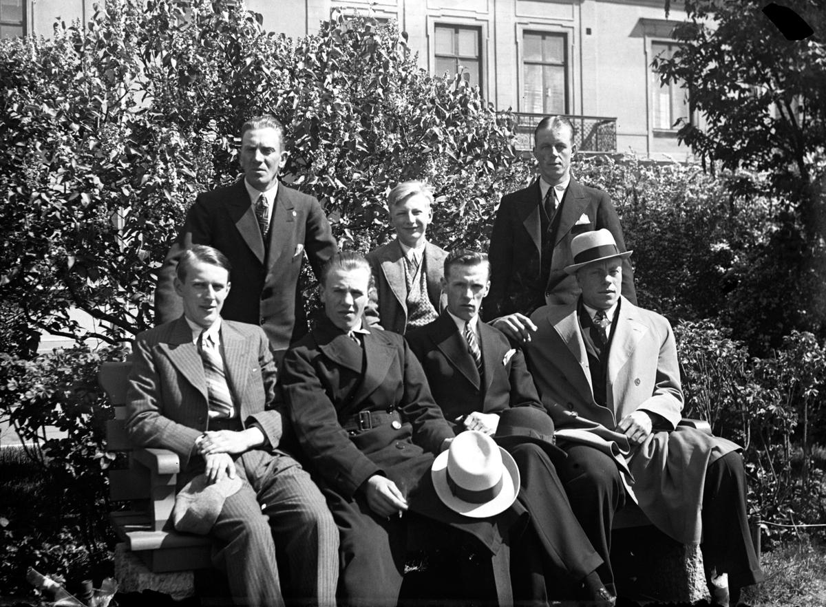 Fyra män sitter på en bänk, bakom den står två män med en pojke mellan sig. I bakgrunden växer buskar och träd framför ett bostadshus.