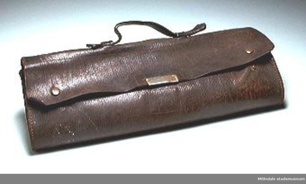 Mörkbrun portfölj med övervikt lock som knäpps i metallspänne på framsidan, handtag och tryckknappar.