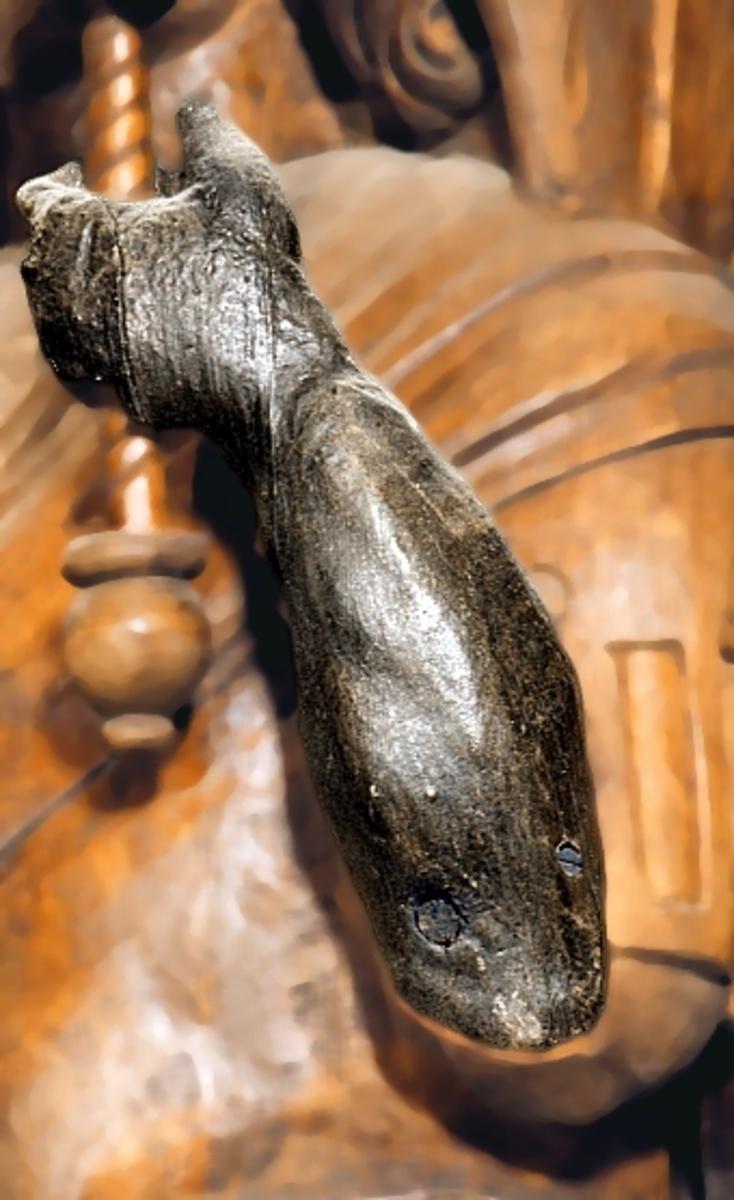 Skulpturdel; nederdelen till en krökt vänsterarm. Två tapphål i fästet. En spricka i handen.  Text in English: Part of a sculpture; the lower section of a curved left arm. Two tapholes in the socket.