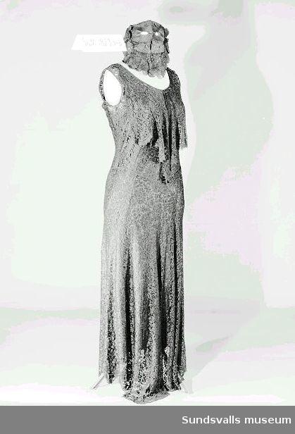 Lång klänning av svart sidenspets med fastsydd underklänning i helsiden. Till klänningen hör en maskeradmask.