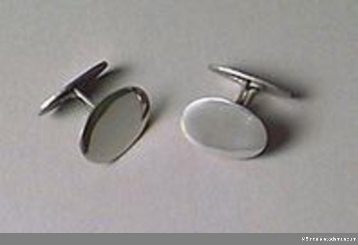 Ett (1) par manschettknappar med ovala, blanka brickor. Den ena är större än den andra.
