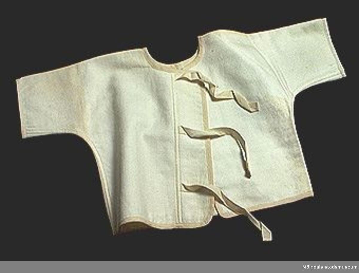 Barnskjorta av kimonomodell i flossad naturvit bomull. Knytes omlott.Elevarbete från textillärarseminariet.Tidigare sakord: skjorta, barn.Gåvan förmedlad genom Gustav Wickström.