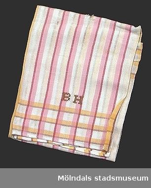 Vit handduk i halvlinne (50% linne och 50% bomull) med ränder i brunt, gult, mörk-och ljus rosa. Korsstygnsmonogram BH i brunt.Flera hål på mitten av handduken.