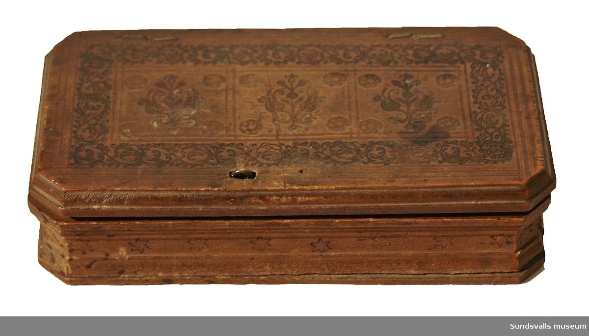 Viktsats bestående av våg med balansarm och skålar av järn. Trettiotre (33) vikter i mässing med olika motiv och text. Fodral i trä med 14 fack i övre och 18 fack i sidolådan till vikterna. Tryckt etikett i locket med vikterna avbildade, 'Döden och mynthandlaren', samt Guilliam de Neve 1627. Vikternas mått: 1,5 x 1,5 cm.