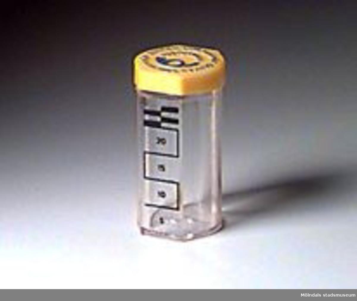 """Rör i genomskinlig plast med gult plastlock. Text i blått på locket: """"BANKEN SOM ALLA NÅR/POSTBANKEN"""", samt postens logotype posthornet i blått i mitten. I botten står i relief i plasten: """"FÖR 1-KRONOR"""". Angivet med streck samt talen 5, 10, 15 och 20 på sidan hur många kronor som finns i röret. Kan innehålla tjugofem kronor som mest."""