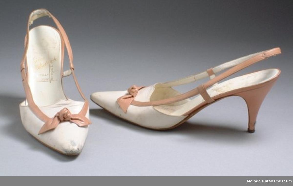 Vit sko med beige klack och öppen häl. Det går ett beige band från tå till häl. Vid tån sitter en beige rosett.Måtten:Stl. 37 1/2, längd 250 mm, bredd 80 mm, höjd 80 mm (klack).