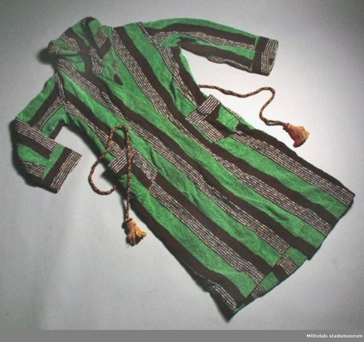 En badrock , grön/brun- och vitrandig med snodd i bruna färgtoner. Låg tillsammans med klädpåse (MM03434) med dateringen 14 oktober 1937.