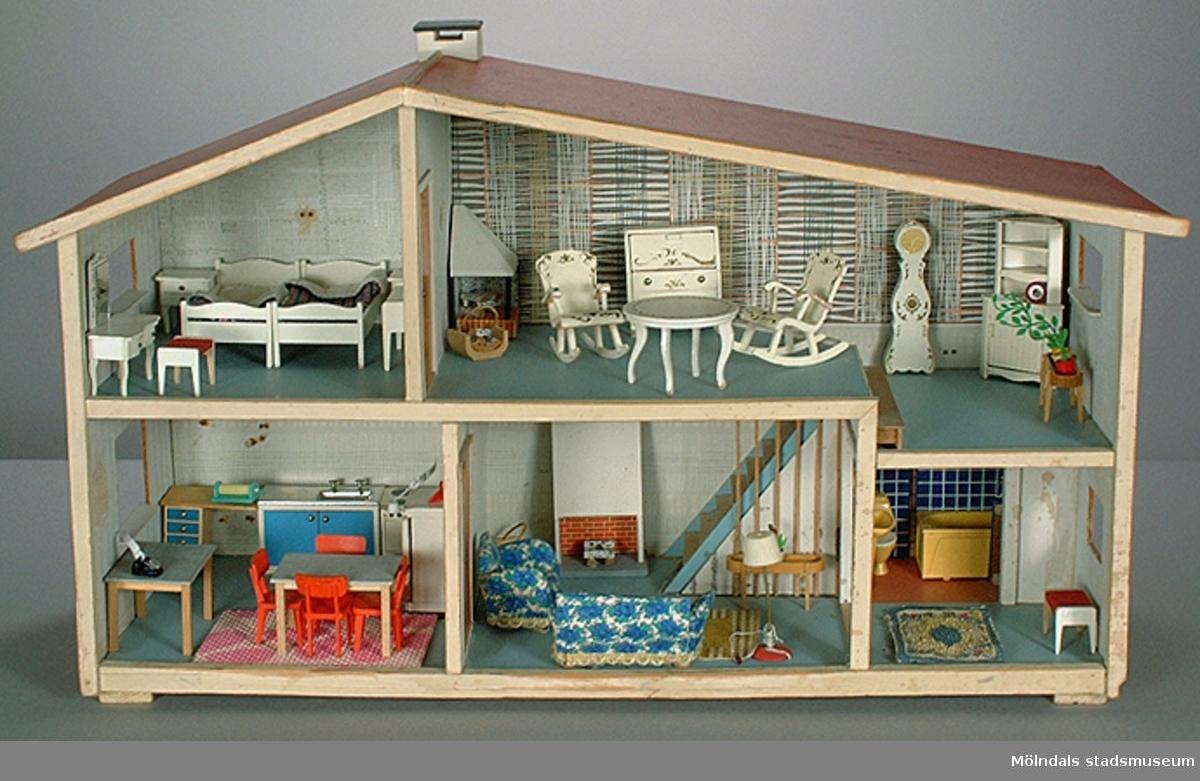 """Toalettstol i gul plast fastsatt på kakelmönstrad,blå masonitskiva. Hör till dockskåp MM03740:1-35.Givaren hade dockskåpet ihop med sin tvillingsyster Birgitta (Bibi). Det var en gåva från mormor, och ingen av kamraternahade ett så fint dockskåp. Givaren berättar att hon lekte med dockor """"långt efter att andra slutat"""".Familjen bodde på Lekskolegatan i Mölndal. Mamman var hemmafru tills givaren var 17 år. Pappan arbetade som byggnadsingenjör."""