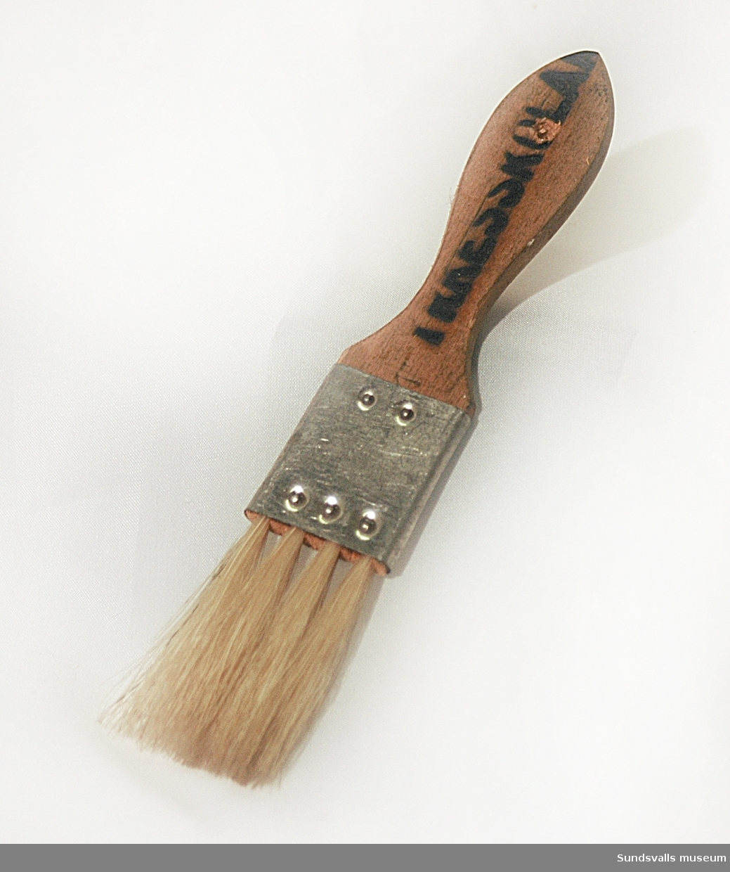 Pensel med fyra borst. Penseln användes på Yrkes- och lärlingsskolan i Sundsvall där Gustaf Walles (1892-1972) undervisade i fackteckning och målning med materiallära från 1929 och 36 år framåt. Texten YRKESSKOLAN finns bränt in i penselns skaft.