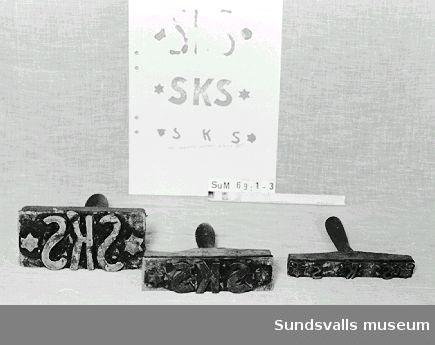 Stämpel i gummi med handtag i trä. Stämpeln visar bokstäverna SKS. Röda färgrester finns kvar på stämpeln.