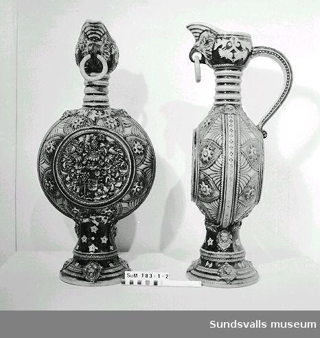 SuM 0183:1-2 prydnadskrus i saltglaserat stengods. Oval form på rund trumpetformad fot. Cylindrisk hals. Uppsvängt snås i form av en fågel med en fritt hängande ring i näbben. Svängd hänkel. Reliefdekor i nyrenässansstil med vapen, årtalet 1588, samt maskaroner. Tillverkad i Tyskland, 1800-talets slut.
