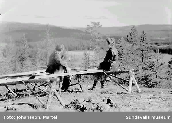 Två kvinnor som sitter på bänk och tittar på utsikten.