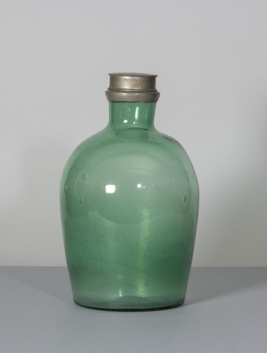 Flaska i glas, ljust grön till färgen. Stor och bukig med bred hals. Skruvlock i tenn.