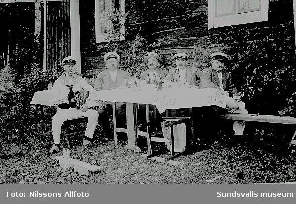 Män sitter vid ett bord utanför en timrad byggnad.