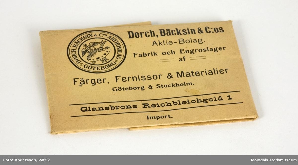 """Förgyllningspulver, använt på Papyrus. Från ca 1910.Pulvret är invikt i två sorters papper. Innerst, ett vitt, glättat papper, inslaget i ett brunt papper med texten """"Glansbrons Reichbleichgold 1"""", från """"Dorch, Bäcksin & C:os Aktie-Bolag. Fabrik och Engroslager af Färger, Fernissor & Materialer, Göteborg & Stockholm""""."""