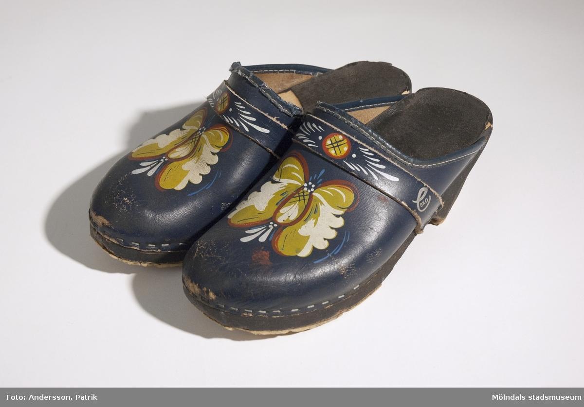 """Ett par blå träskor med kurbits målning.Under sulan står det tryckt: """"Vollsjö Made in Sweden"""". På skons ovansida, på ytterkanten står signeringen: """"e SKO"""" i silverfärg.Skorna är något nötta och slitna.MåttLängd: 240 mm,  Bredd: 93 mm,  Höjd: 105 mm.Givaren Monika fick detta par av sin dotter till Mors dag 1976. Dottern hade ett par likadana träskor.Den vanligaste modellen av träko i Sverige är den med sula i trä och ovandel i läder. Äldre modeller är vanligen helt i trä och efterliknar skor av läder. Vollsjö är en känd tillverkare av träskor och deras skor har även fått märkesnamnet Vollsjötoffeln efter orten."""